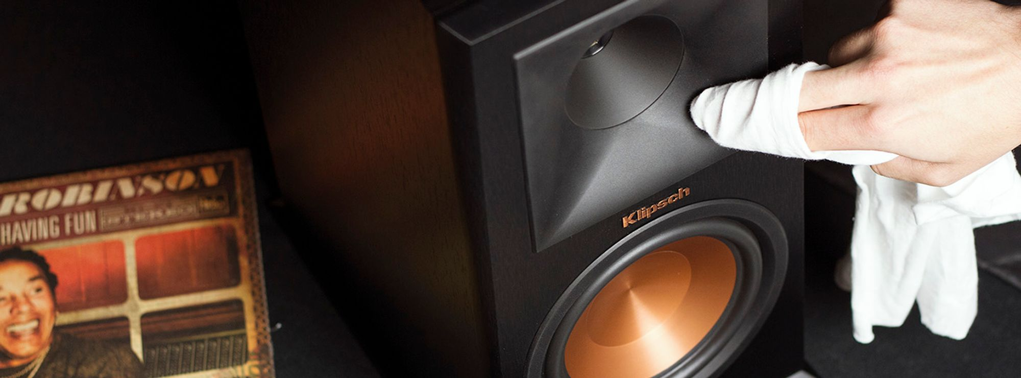 Person wiping a Reference Premiere speaker clean